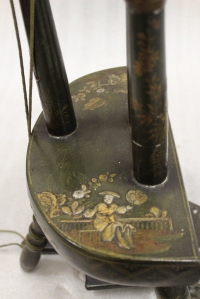 Part of a spinning wheel in the Superstore decorated with Chinese figures.