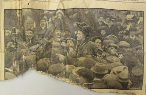 Man wearing hat, surrounded by lots of other men, looks like a working class scene. I might guess that it is to do with a labour dispute, possibly a strike? It looks like a very interesting photograph, but without the rest of the newspaper which would hold the corresponding story I am unable ascertain what it is about.